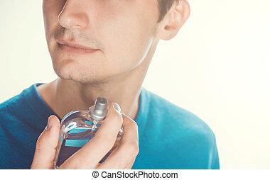Young man applying perfume