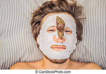Young man makes a face mask with snail mucus. Snail crawling on a face mask. SPA for man, SPA for all