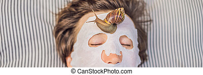 Young man makes a face mask with snail mucus. Snail crawling on a face mask. SPA for man, SPA for all BANNER, LONG FORMAT