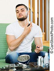 Young man spraying fragrance perfume