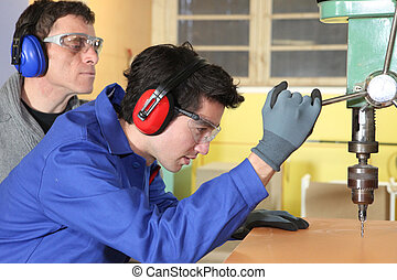 Young man using a bench drill