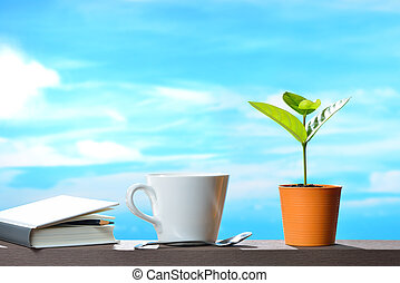 Young plant in pot with cup of coffee and book on sky background