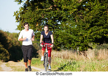 Young sport couple jogging and cycling
