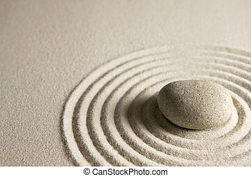 Close-up of a stone on raked sand; zen concept